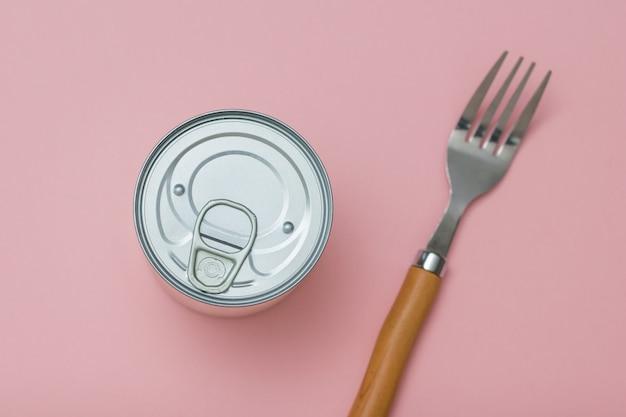 ピンクの背景にブリキ缶とフォーク。缶詰用のユニバーサルコンテナ。