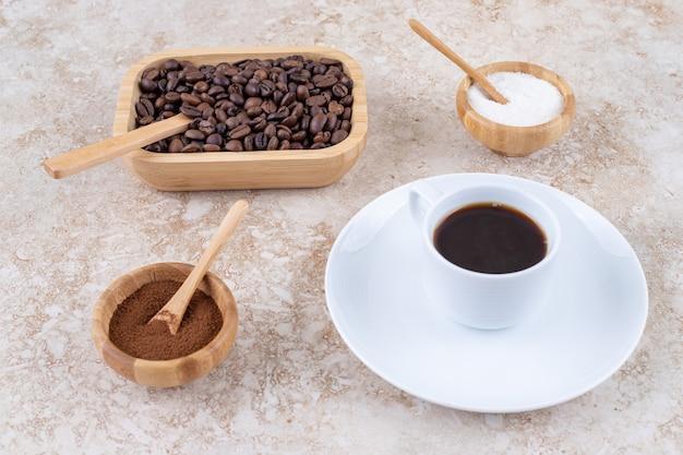 さまざまな形のコーヒーの横にある小さな砂糖のボウル