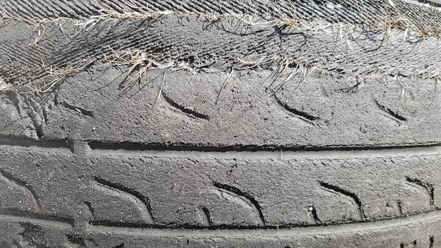 Шина, поврежденная после длительного использования. изношенная и порванная автомобильная шина на свалке.
