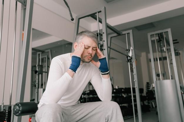 激しいトレーニングの後、疲れたアスリートが頭を抱えて座っています。頭痛。カーディオワークアウト