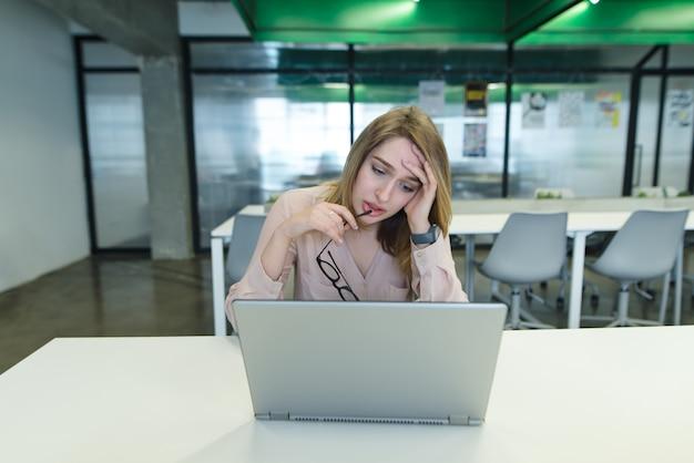 疲れた美しい少女がオフィスのラップトップで働いています。