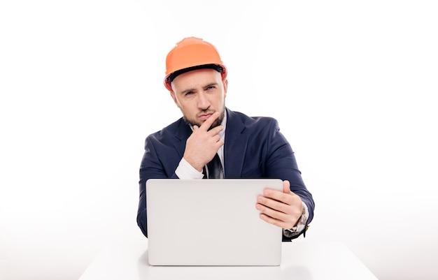 주황색 헬멧에 피곤한 생성자 사업가 노트북 화면을보고 건설 프로젝트를 연구합니다. 테이블에 앉아서 커피를 마신다