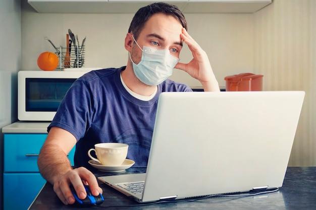 疲れた従業員はホームオフィスで働いています。テーブルの上のラップトップでコロナウイルスの発生のためにホームオフィスから職場で医療用フェイスマスクを身に着けている若い男。リモートワーク。