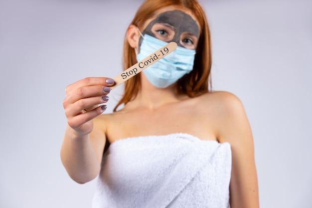 미용 마스크를 얼굴에 쓰고 또 다른 전염병에 걸린 살롱에서 피곤한 소녀가 중지 바이러스를 보여줍니다. 미용, 스파, 건강 및 covid 19 개념. 고품질 사진