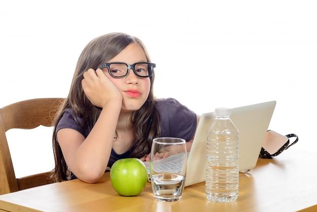 Усталая маленькая девочка со своим компьютером и яблоком