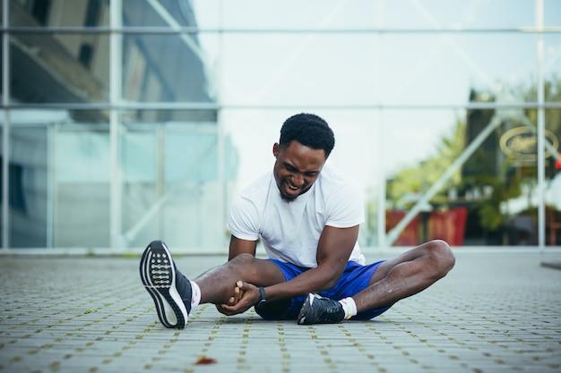 ランニング後の疲れた男性が足をマッサージし、膝と筋肉に激しい痛みがあります