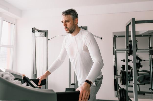 땀에 젖은 티셔츠를 입은 피곤한 남자가 스포츠 클럽의 러닝 머신에서 뛰고 있습니다. 심장 훈련. 현대 체육관