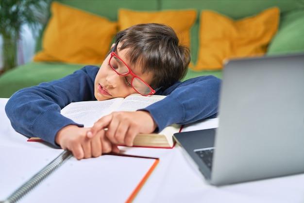 Усталый школьник спит за столом, делая домашнее задание, домашний интерьер