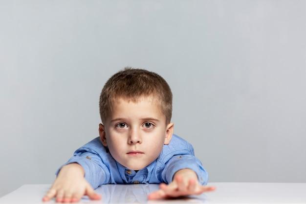 피곤한 남학생 소년은 팔을 앞으로 뻗은 채 테이블에 앉는다.