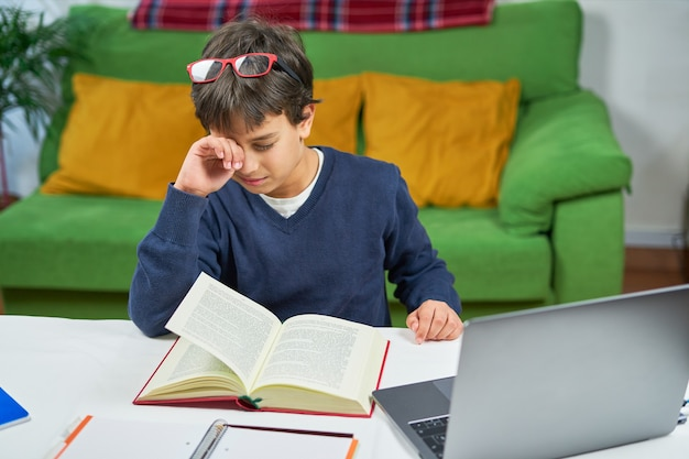 Усталый мальчик-студент учится дома, протирая глаза
