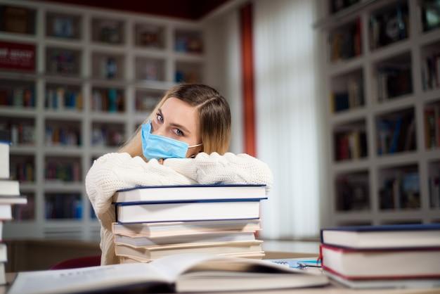 学校の図書館で勉強している顔の保護マスクで疲れた学生。