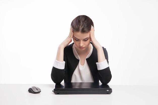흰색 배경에 격리된 노트북 앞에 있는 피곤한 여자