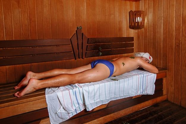 Уставший молодой человек лежит на полке в ванной.