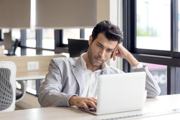 Усталые глаза молодого человека устали от работы за компьютером