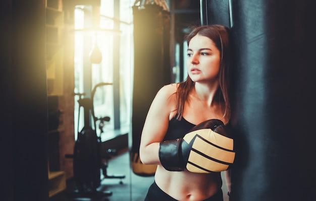 サンドバッグで重いボクシングのトレーニングの後に休んでボクシンググローブで疲れた若いスポーツの女性。