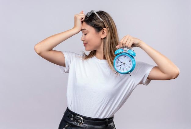 頭に手を保ちながら青い目覚まし時計を保持しているサングラスの白いtシャツで疲れた若い女性