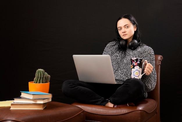 一杯のお茶のヘッドフォンとラップトップを持っている疲れた若い女性は家から働きます