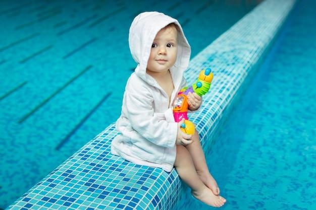 Малыш, маленький ребенок в банном полотенце в бассейне с яркой игрушкой в руках.