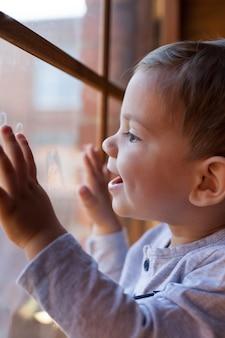 한 유아 소년이 창문 옆에 서서 유리 잔 위에 그림을 그리고 혀를 내밀고 유리 잔을 핥습니다.