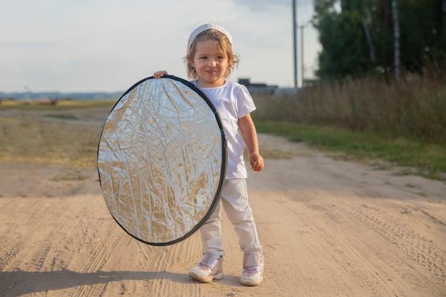 幼児は田舎道で写真家のための反射板を持っています。小さなヘルパーアシスタント