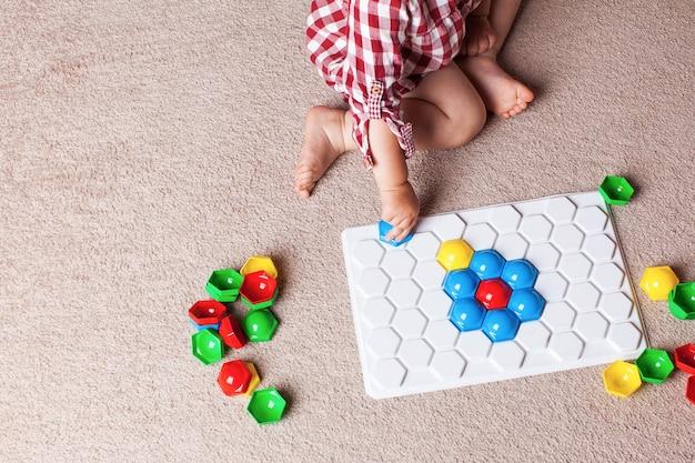 Малыш играет с пластиковой мозаикой на ковре в детской комнате. раннее развитие, метод монтессори.