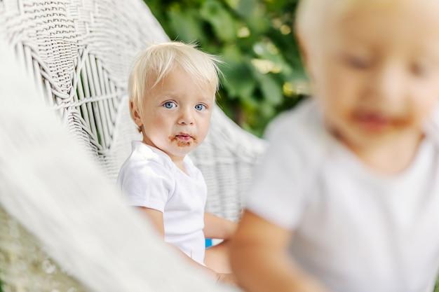 Малыш с голубыми глазами и светлыми волосами с грязным шоколадным лицом сидит во дворе на плетеных стульях и смотрит в камеру. милый малыш любит сладкое. смешная картинка с младенцем