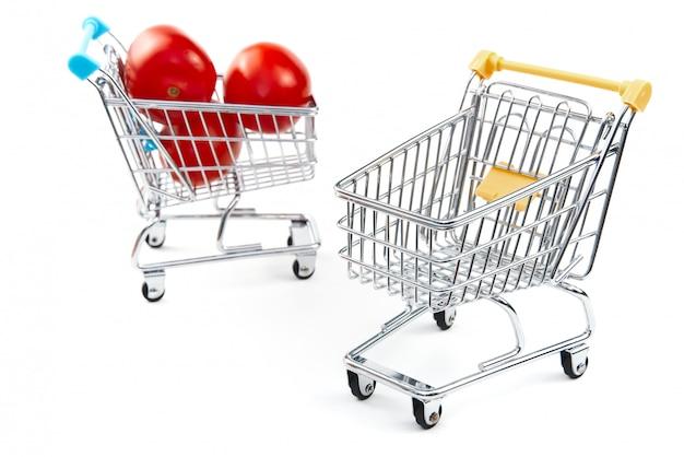 白い背景で隔離のショッピングカートのトマト。ショッピングカートで熟したおいしい赤いトマト。トマト取引の概念。オンラインショッピングの概念。カートと白い背景の上のトマト。