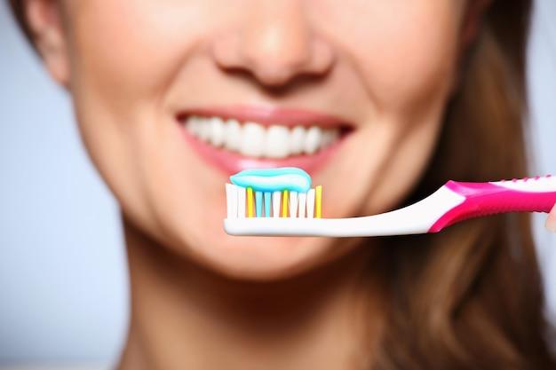 Зубная щетка с пастой и красивая улыбка на заднем плане