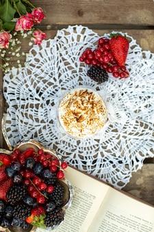 Сверху крупным планом вид кофе вкусный вместе с разноцветными ягодами на белой ткани и коричневой деревянной поверхности
