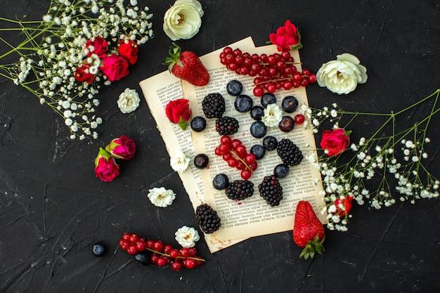 Вид сверху крупным планом свежие ягоды окрашены в разные красные ягоды и ежевики на бумаге и темном полу