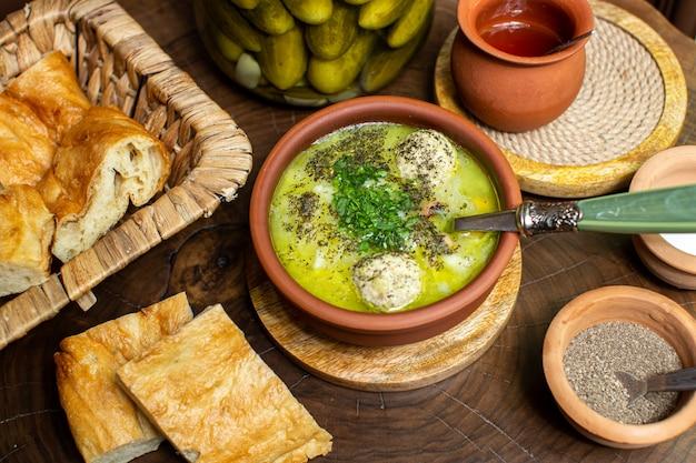 Вид сверху, горячий суп в коричневом круглом горшочке, нарезанный соленый огурец, хлеб и специи
