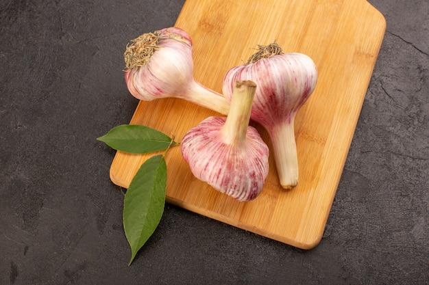 Верхний закрытый вид весь чеснок спелый свежий изолирован на коричневом деревянном столе и серый