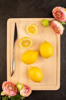 上部の遠くから見る新鮮なレモンが熟した全体を酸っぱくし、暗い机の上でまろやかな柑橘系のトロピカルビタミンイエローをスライス