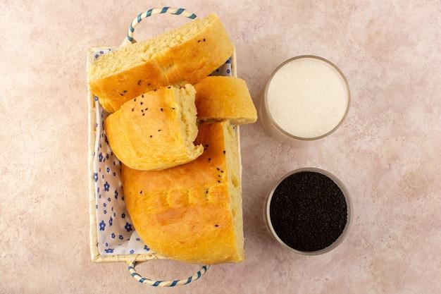 Вид сверху, выпеченный хлеб, горячий вкусный, свежий, нарезанный внутри хлебной корзины с солью и перцем на розовом