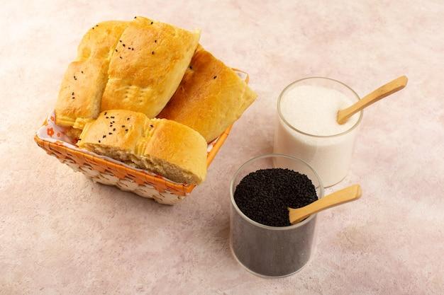 Вид сверху запеченный хлеб горячий вкусный свежий нарезанный внутри хлебницы вместе с солью и перцем на розовом