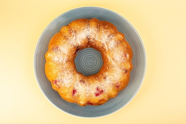 Вид сверху запеченный фруктовый торт вкусный круглый с красной вишней внутри и сахарной пудрой внутри круглой синей тарелки на желтом