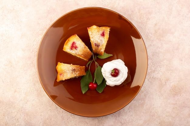 Вид сверху запеченный фруктовый торт, вкусный нарезанный красной вишней внутри и сахарной пудрой внутри круглой коричневой тарелки на розовом