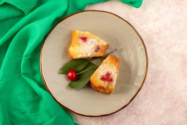 Вид сверху запеченный фруктовый торт вкусные кусочки с красной вишней внутри и сахарной пудрой внутри круглой серой тарелки на розовом