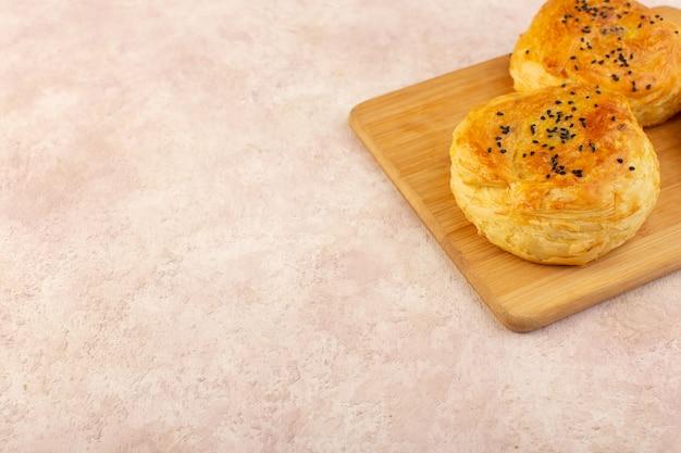 Вид сверху запеченные когалы круглой формы, вкусные горячие свежие из духовки на коричневом деревянном столе