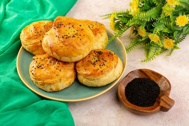 Вид сверху запеченные qogals круглой формы вкусные горячие свежие из духовки внутри зеленой тарелки с цветком