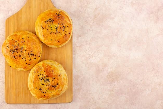 Вид сверху запеченных квогалов круглой формы, вкусных горячих свежих из духовки на коричневом столе