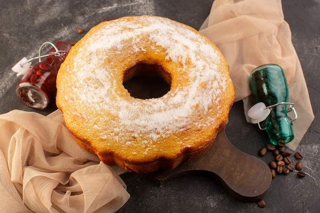 トップビュー木製の机の上の砂糖の粉とコーヒーの種子と丸いケーキを焼いた