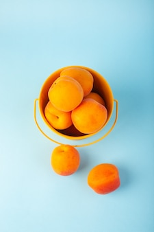 分離された黄色のバスケットの中のアプリコットの甘い新鮮でまろやかな果物のトップビューバスケット