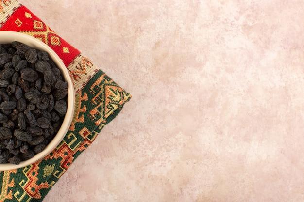 Вид сверху черные сухофрукты внутри круглой тарелки на красочном ковре на розовом