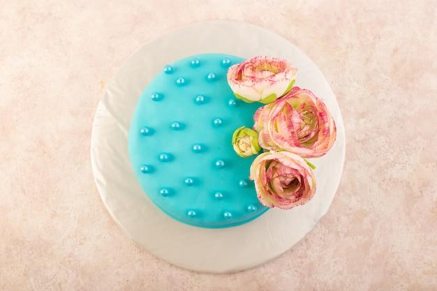 灰色の机のお祝いパーティーの誕生日の色の上に花と上面の青い誕生日ケーキ