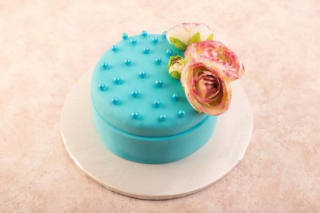 ピンクのデスクのお祝いパーティーの誕生日ケーキの色の上に花が上から見た青い誕生日ケーキ