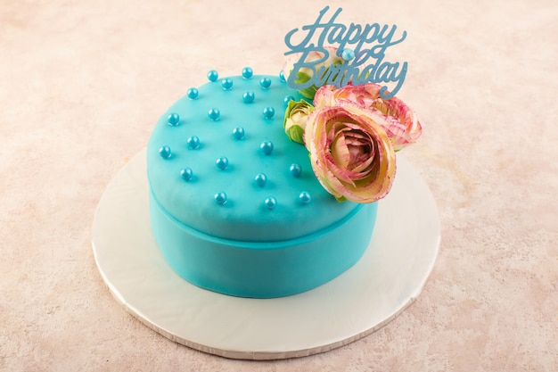ピンクの机のお祝いパーティーの誕生日の上に花と上から見る青い誕生日ケーキ
