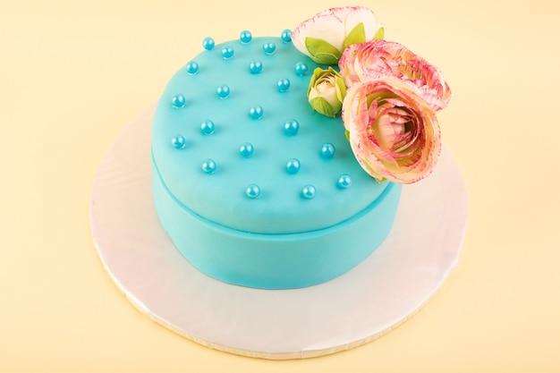 黄色の机のお祝いパーティーの誕生日ケーキの色の上に花を上から見た青い誕生日ケーキ
