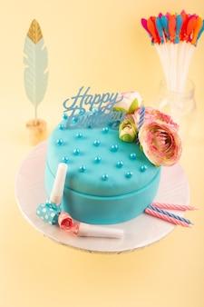 黄色の机のお祝いパーティーの誕生日ケーキの上に花と上から見る青い誕生日ケーキ