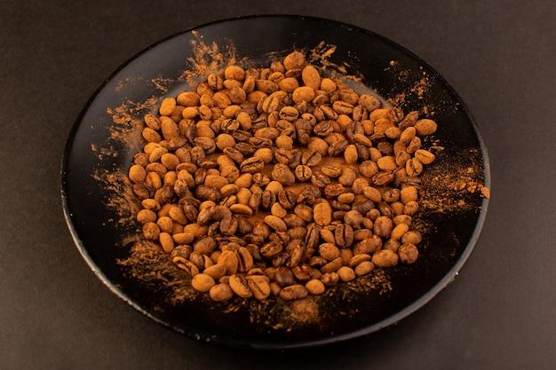 茶色のテーブルの上の黒い皿の中の上面の茶色のコーヒー種子